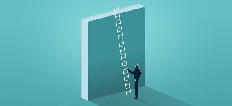 businessman climbing over wall