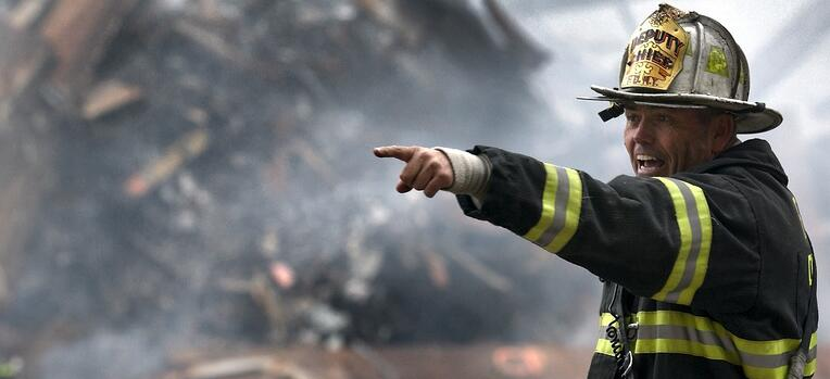 fireman pointing in front of a pile of rubble