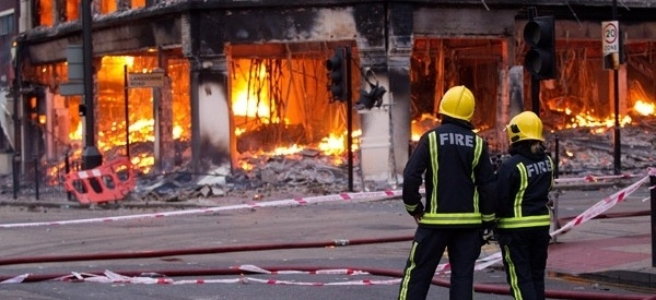firemen standing in front of a burning building
